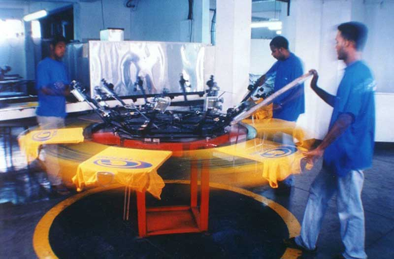 Workers are printing on a Screen Printing Press